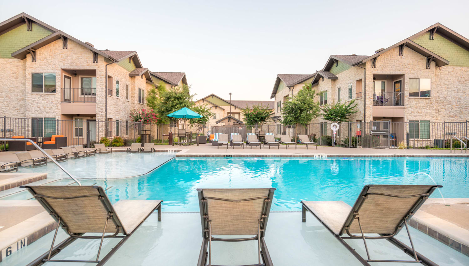 Lounge chairs on the sun deck in the pool at Olympus Waterford in Keller, Texas
