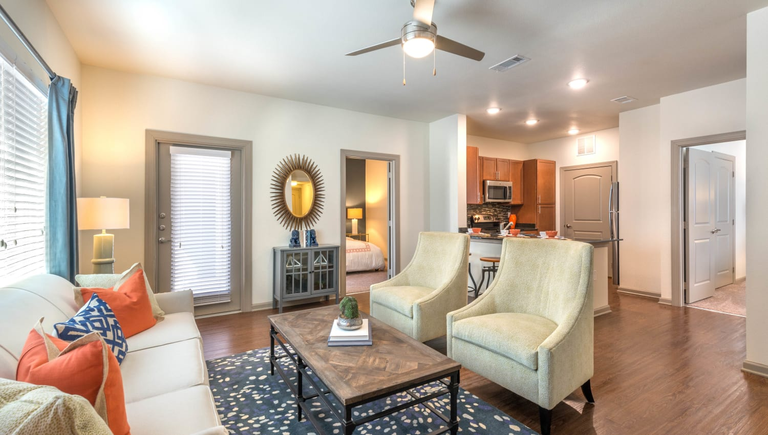 Well-furnished living space with a ceiling fan in a model home at Olympus Waterford in Keller, Texas