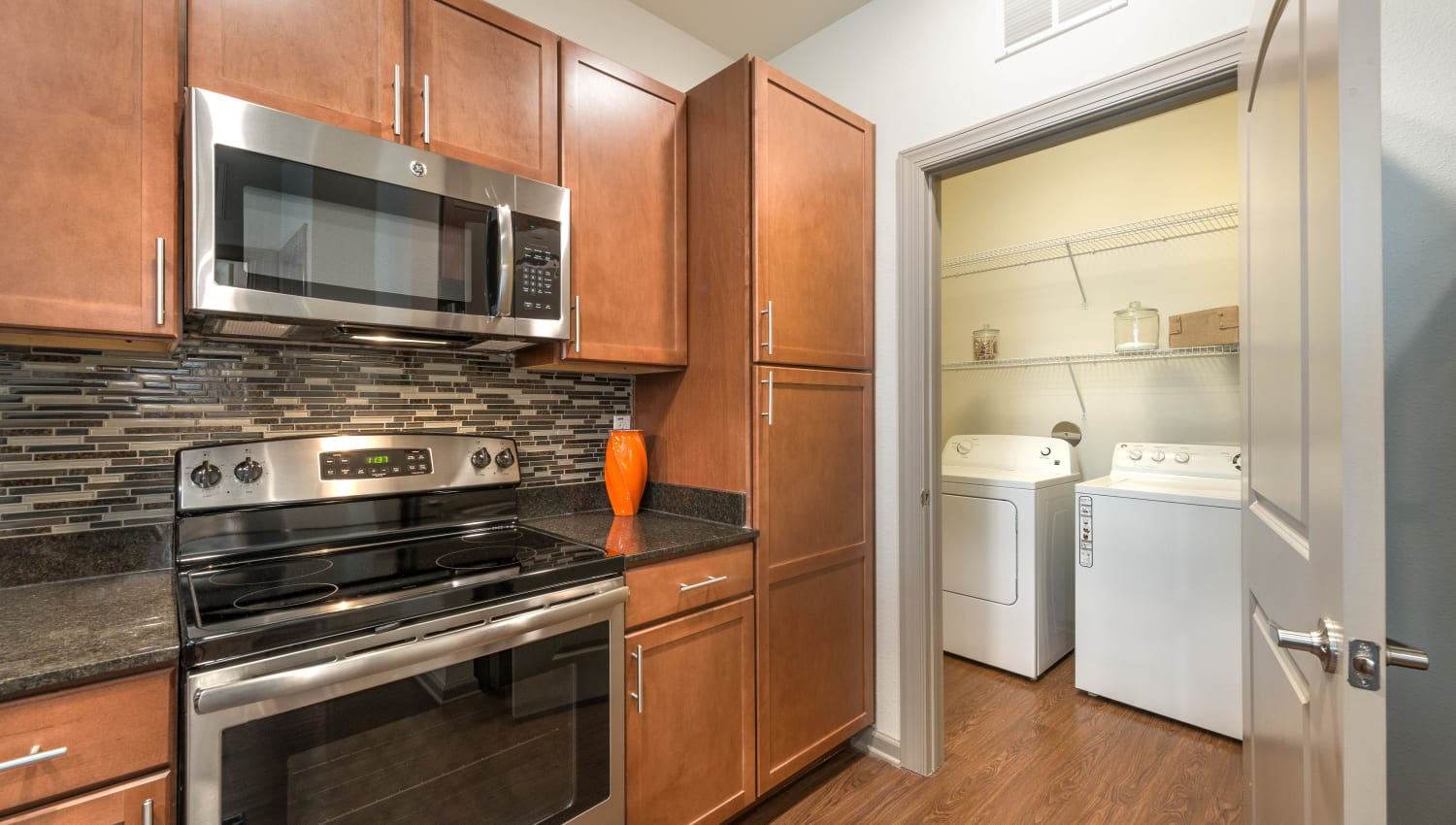 Laundry room next to the kitchen in a model apartment at Olympus Waterford in Keller, Texas