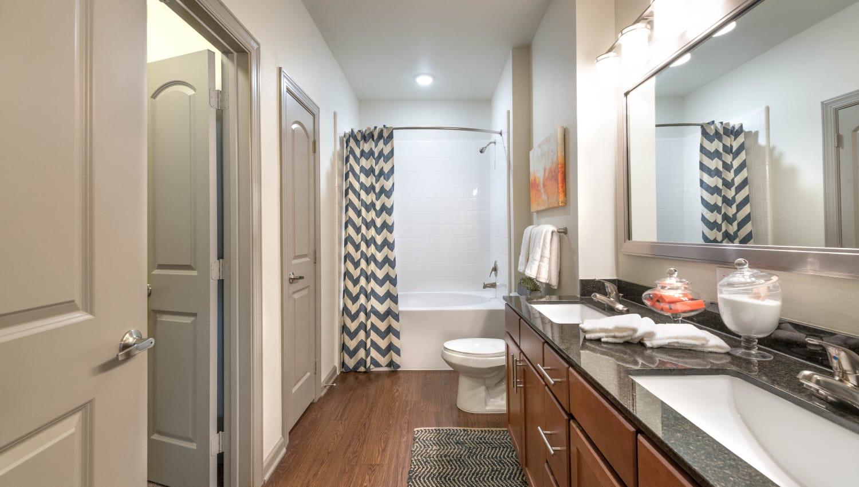 Dual sinks in the en suite bathroom of a model home's master bedroom at Olympus Waterford in Keller, Texas