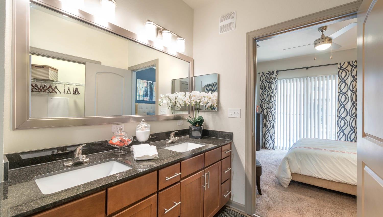 Large vanity mirror in a model home's master bathroom at Olympus Waterford in Keller, Texas