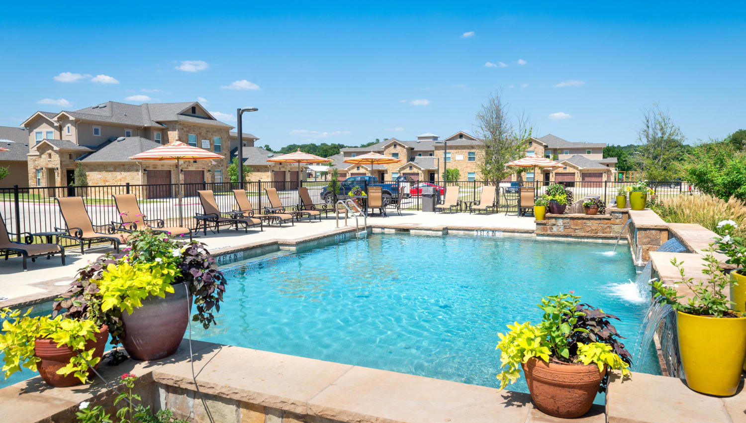 Resort-style swimming pool surrounded by a variety of well-maintained flora at Olympus Willow Park in Willow Park, Texas