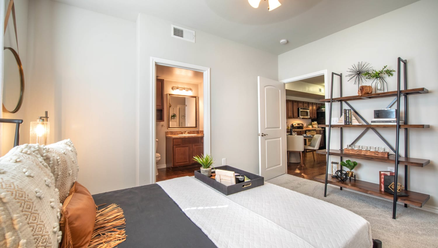 Well-arranged master bedroom with an en suite bathroom in a model home at Olympus Willow Park in Willow Park, Texas