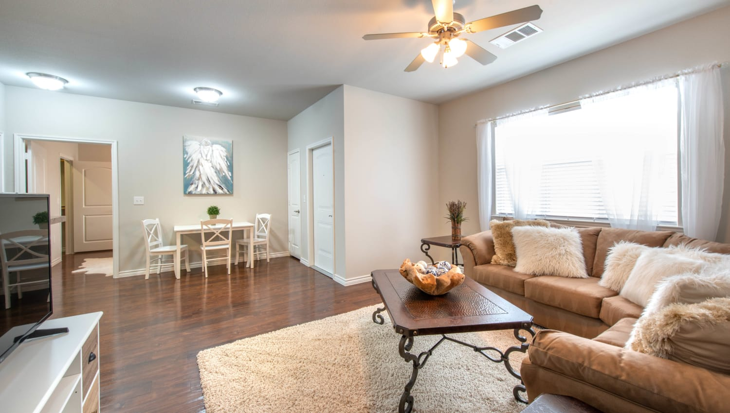 Hardwood floors and a ceiling fan in the comfortably furnished living area of a model apartment at Olympus Willow Park in Willow Park, Texas