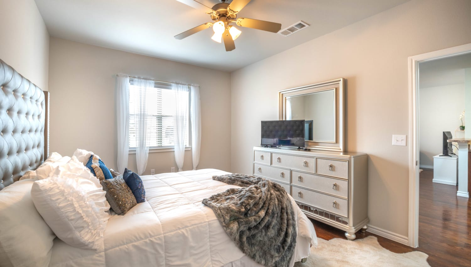 Plush carpeting and a ceiling fan in a model apartment's bedroom at Olympus Willow Park in Willow Park, Texas