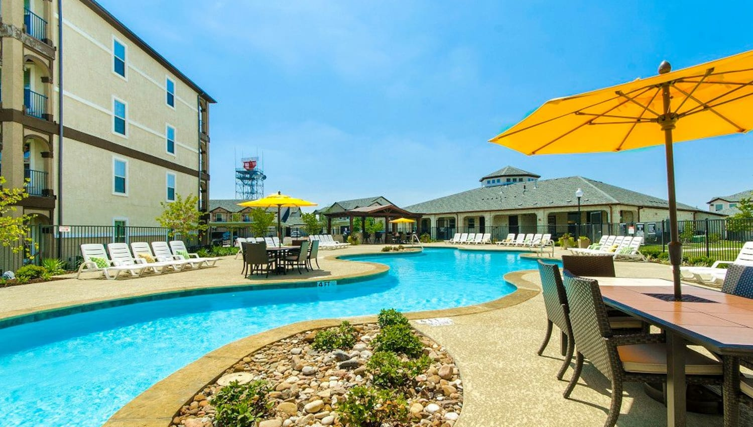 Winding pool with great places to sit in the shade nearby at Olympus Woodbridge in Sachse, Texas
