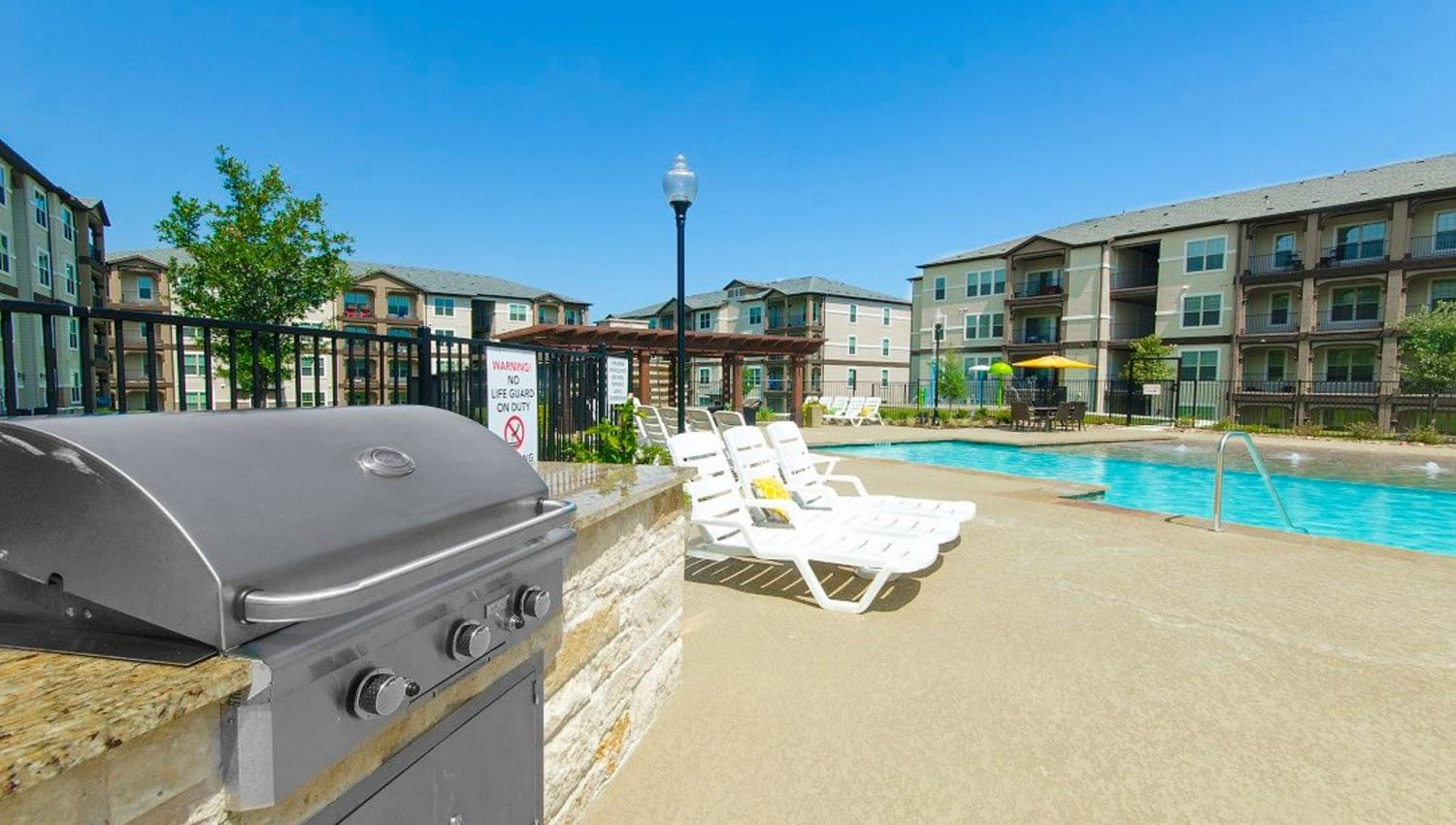 Barbecue area with gas grills near the pool at Olympus Woodbridge in Sachse, Texas