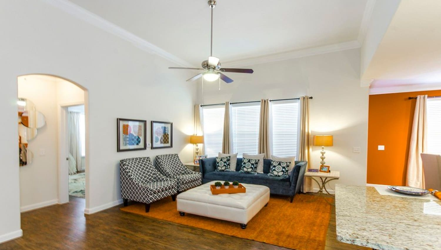 Well-furnished living area with a ceiling fan in a model home at Olympus Woodbridge in Sachse, Texas