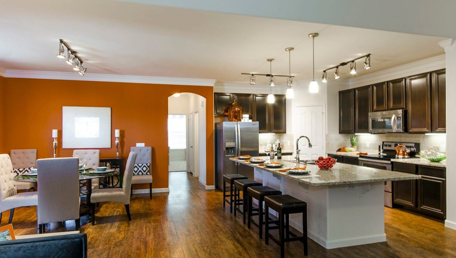 Gorgeously designed open-concept living and kitchen areas with an accent wall and hardwood floors in a model apartment at Olympus Woodbridge in Sachse, Texas
