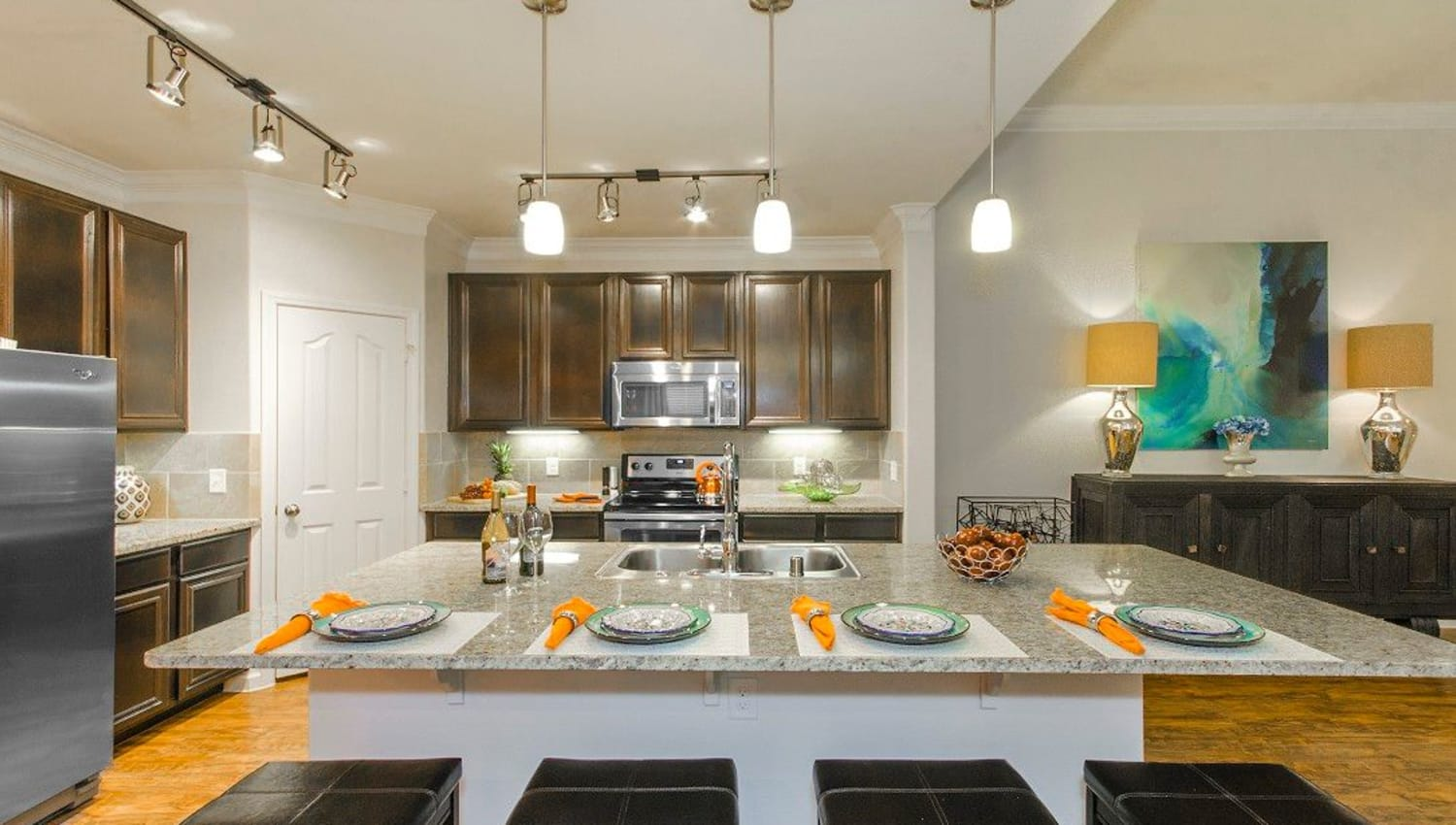 Model home's kitchen with an island and granite countertops at Olympus Woodbridge in Sachse, Texas