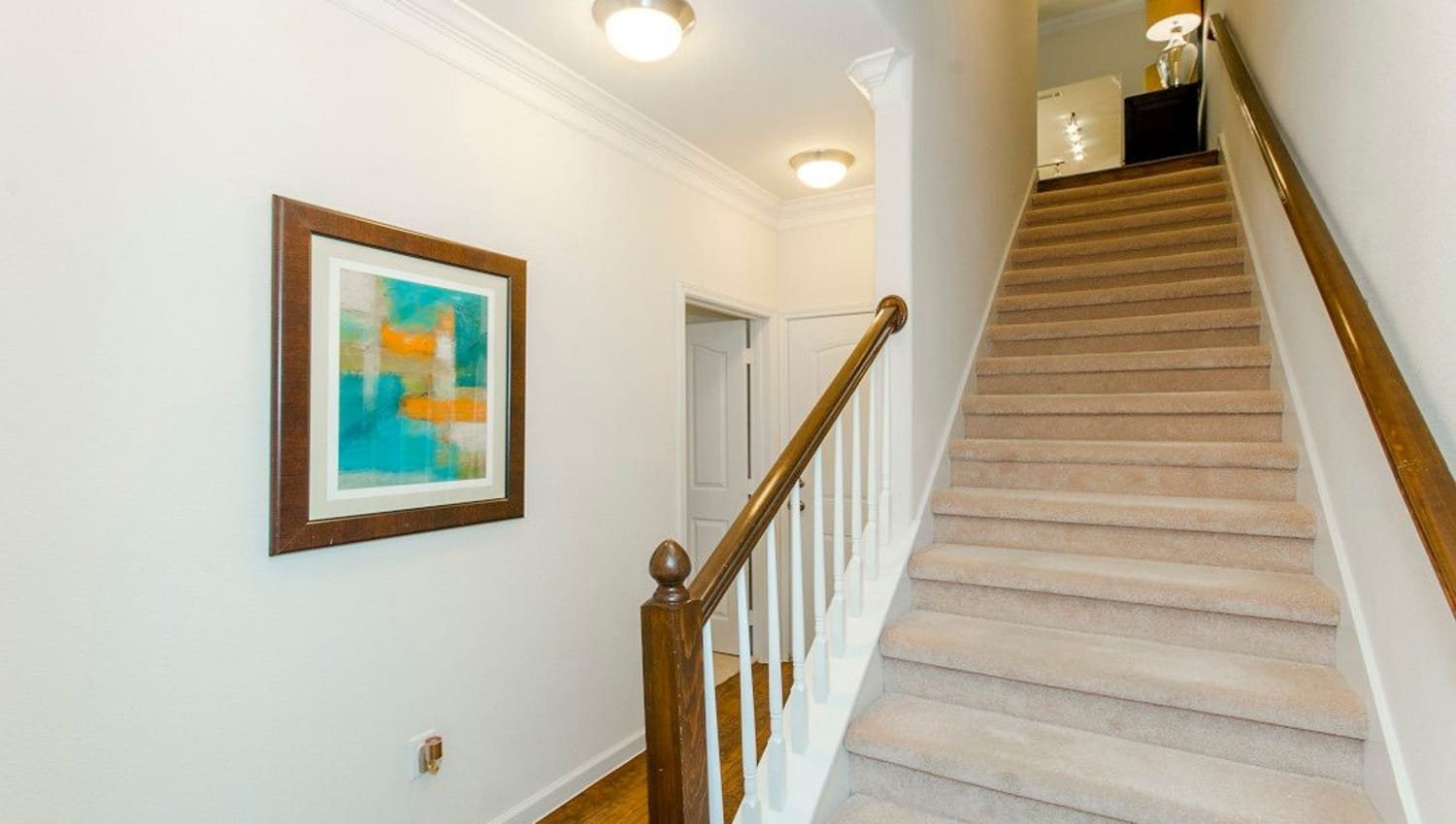 Stairs leading to the upper floor of a model townhome at Olympus Woodbridge in Sachse, Texas
