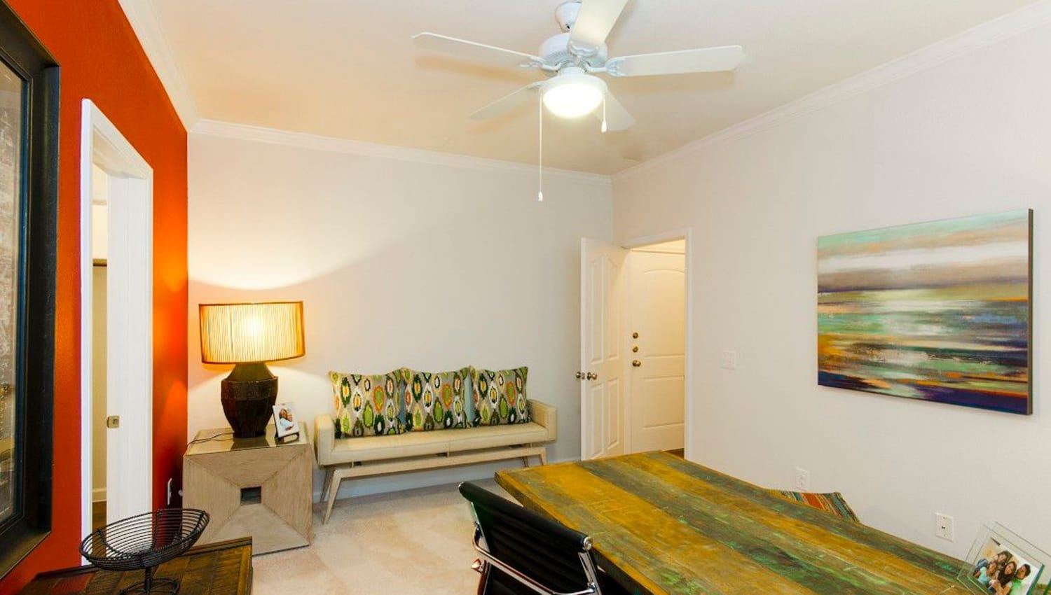 Guest room with an accent wall and a ceiling fan in a model home at Olympus Woodbridge in Sachse, Texas