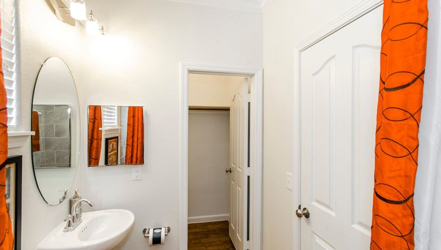 Bathroom with extra closet storage in a model home at Olympus Woodbridge in Sachse, Texas