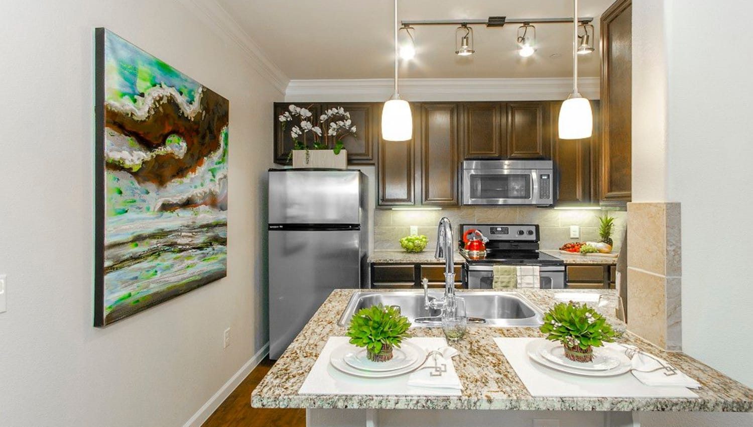 Stainless-steel appliances and custom lighting in a model home's kitchen at Olympus Woodbridge in Sachse, Texas