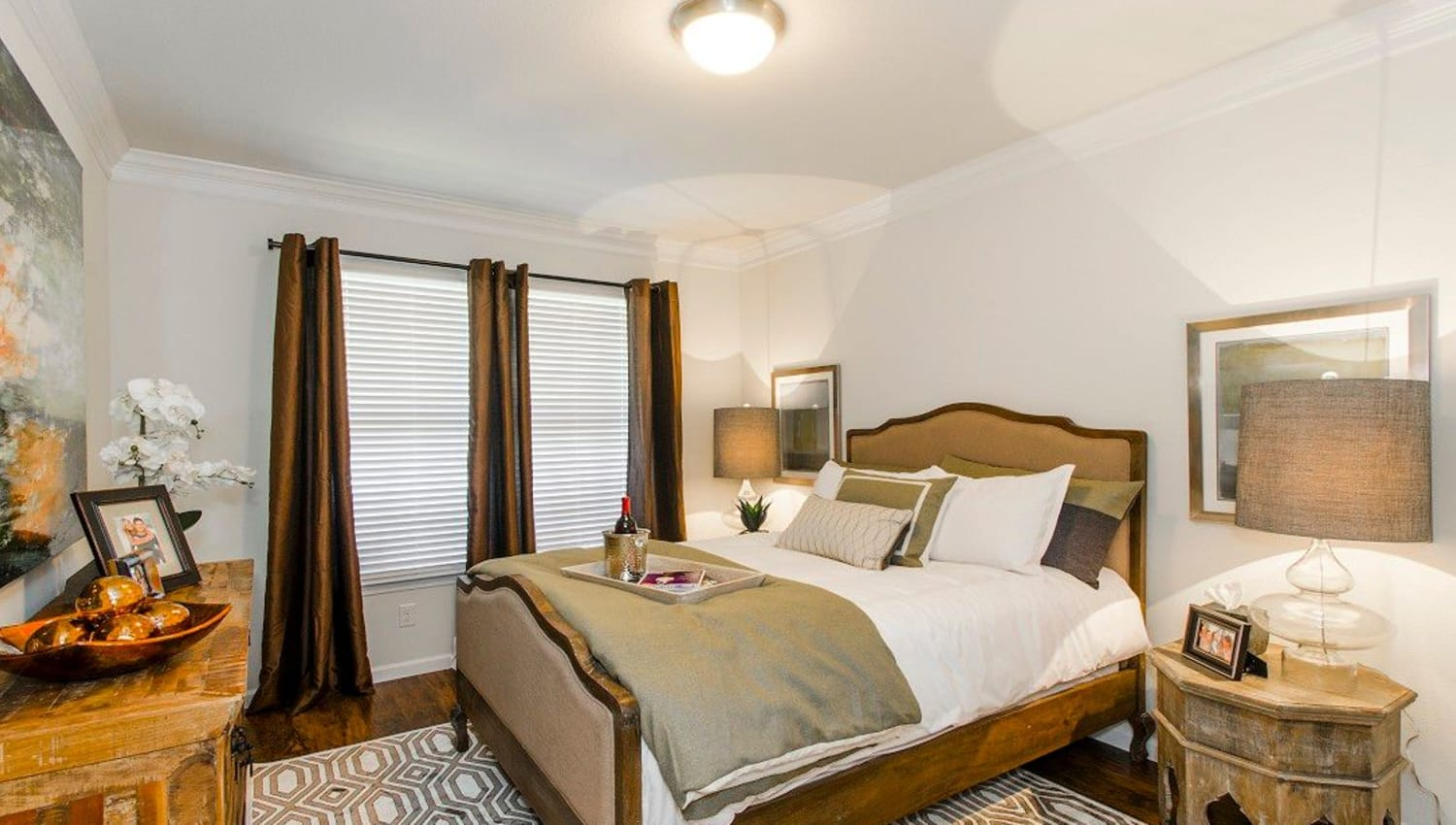 Draped windows and a ceiling fan in the master bedroom of a model townhome at Olympus Woodbridge in Sachse, Texas