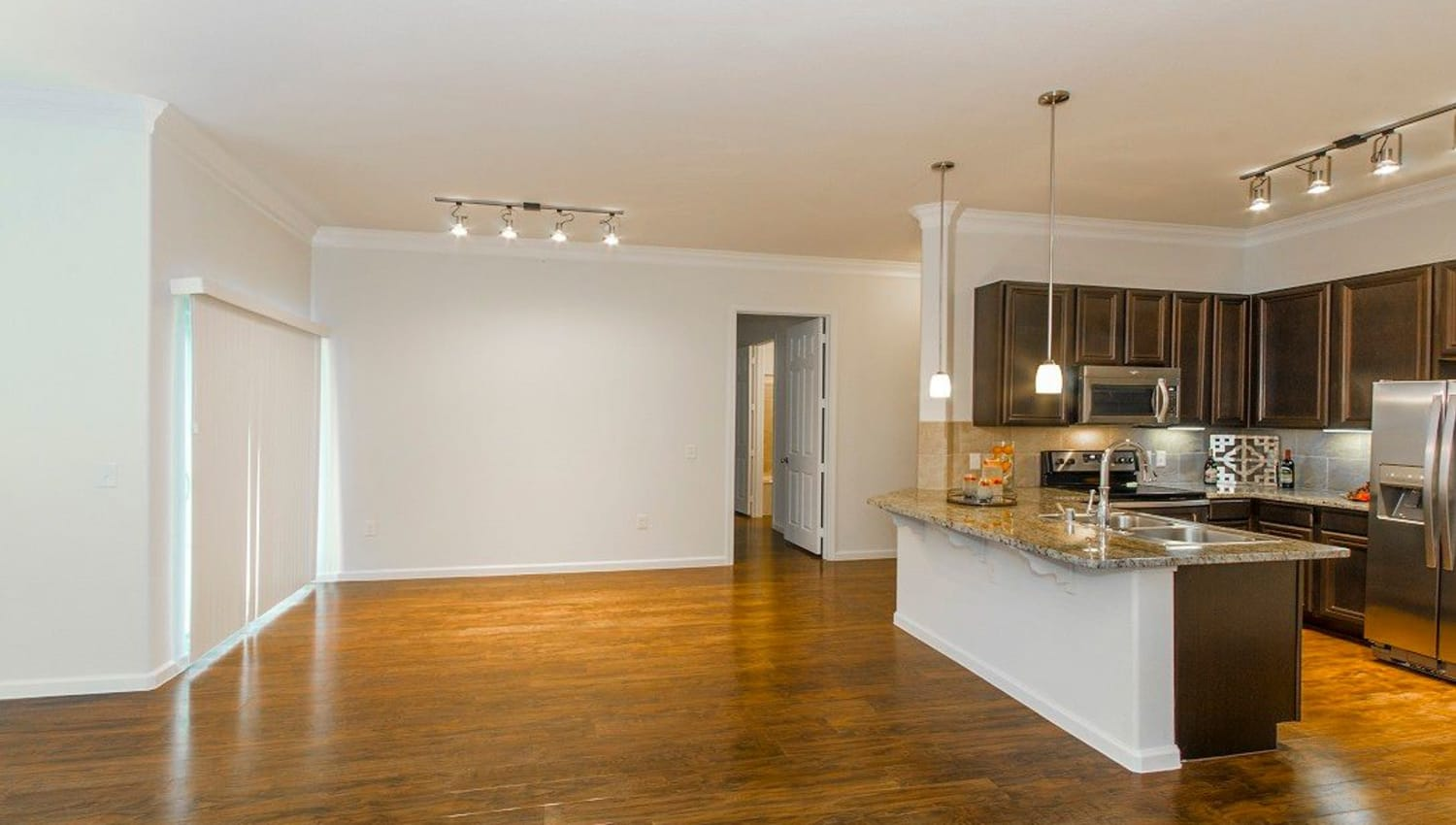 Beautifully finished hardwood floors throughout the living areas of a model home at Olympus Woodbridge in Sachse, Texas