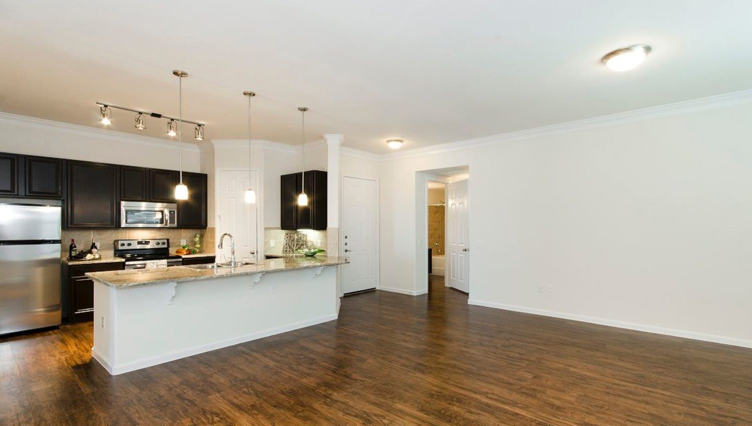 Large open-concept living area and kitchen in a model apartment at Olympus Woodbridge in Sachse, Texas