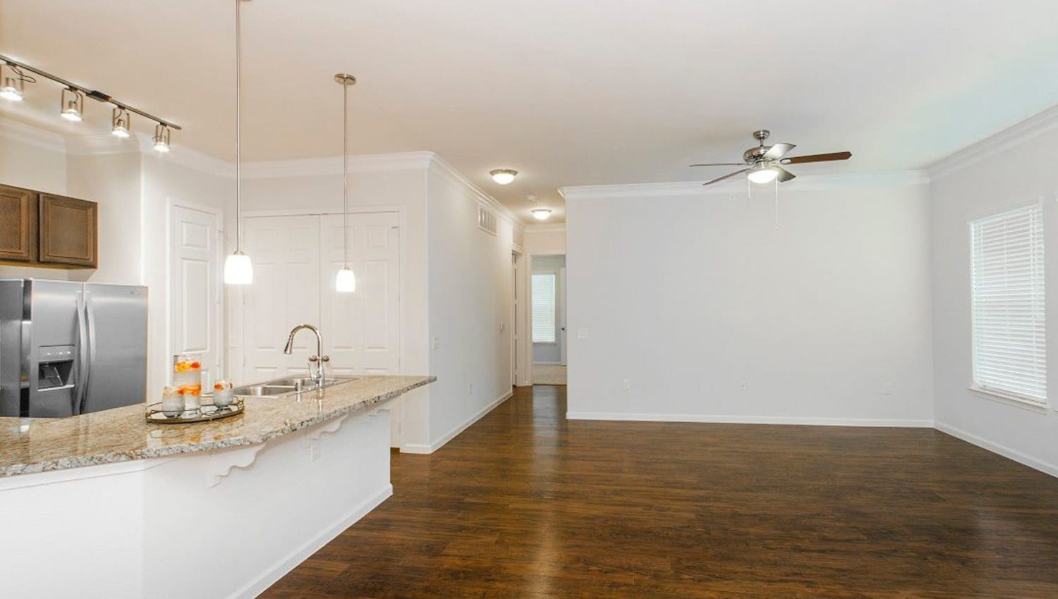 Ceiling fan and hardwood flooring in the living areas and kitchen in a model home at Olympus Woodbridge in Sachse, Texas