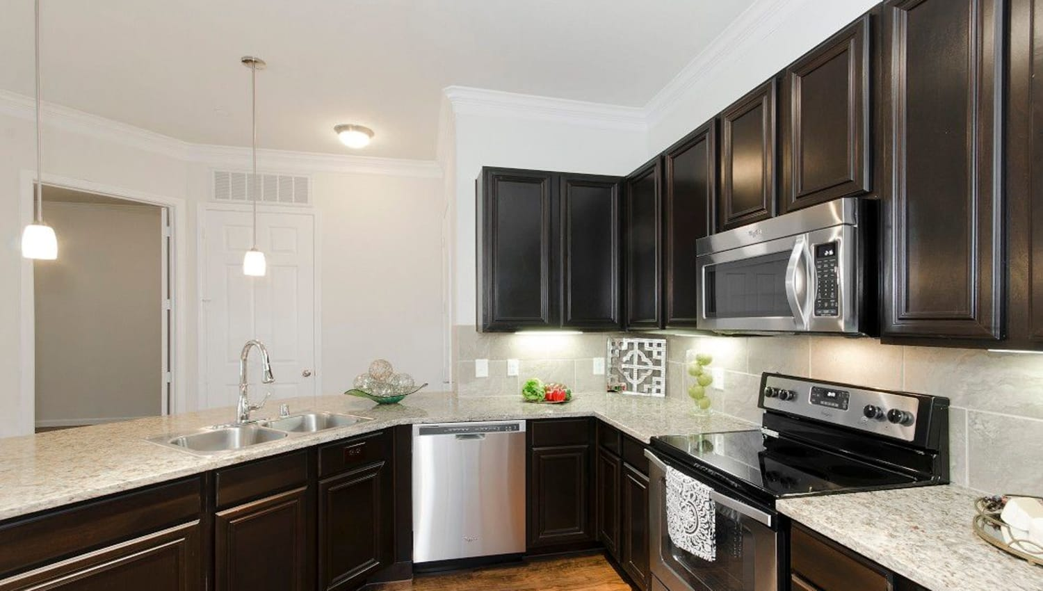 Espresso cabinetry and granite countertops in a model townhome's kitchen at Olympus Woodbridge in Sachse, Texas