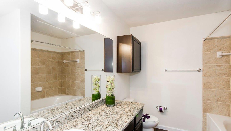 Granite countertop in a model apartment's bathroom at Olympus Woodbridge in Sachse, Texas