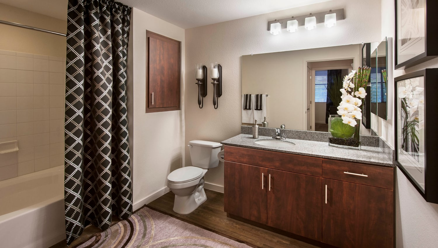Master bathroom with a tiled shower and large vanity mirror in a model home at Redstone at SanTan Village in Gilbert, Arizona