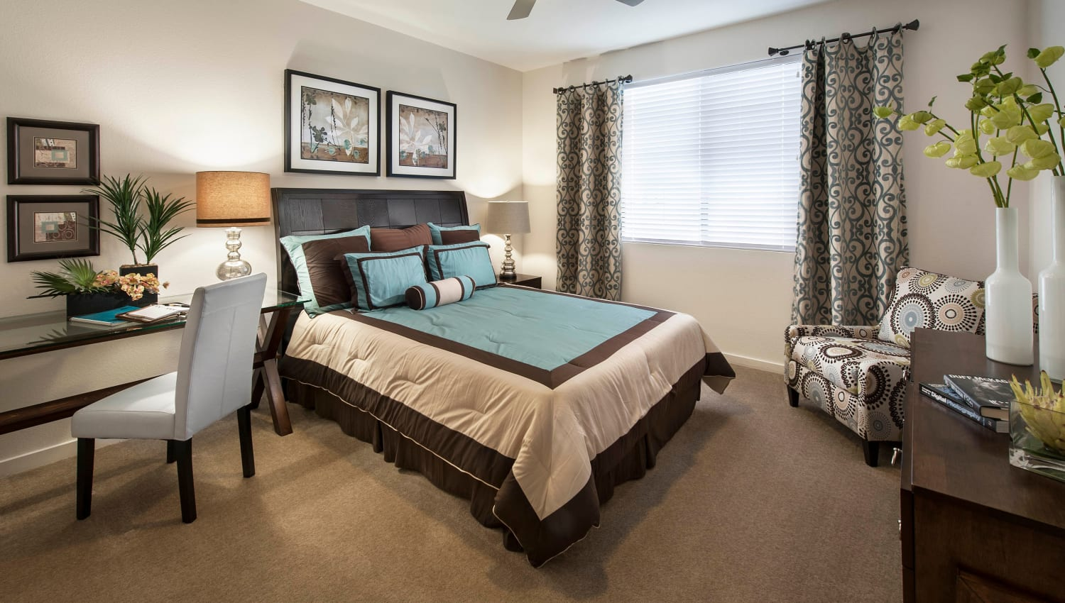 Draped bay windows and plush carpeting in a model home's master bedroom at Redstone at SanTan Village in Gilbert, Arizona