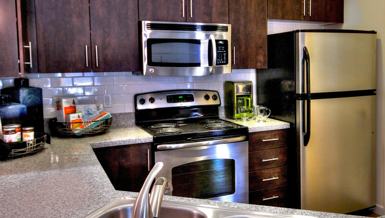 Dark wood cabinetry in a model home's kitchen at Redstone at SanTan Village in Gilbert, Arizona
