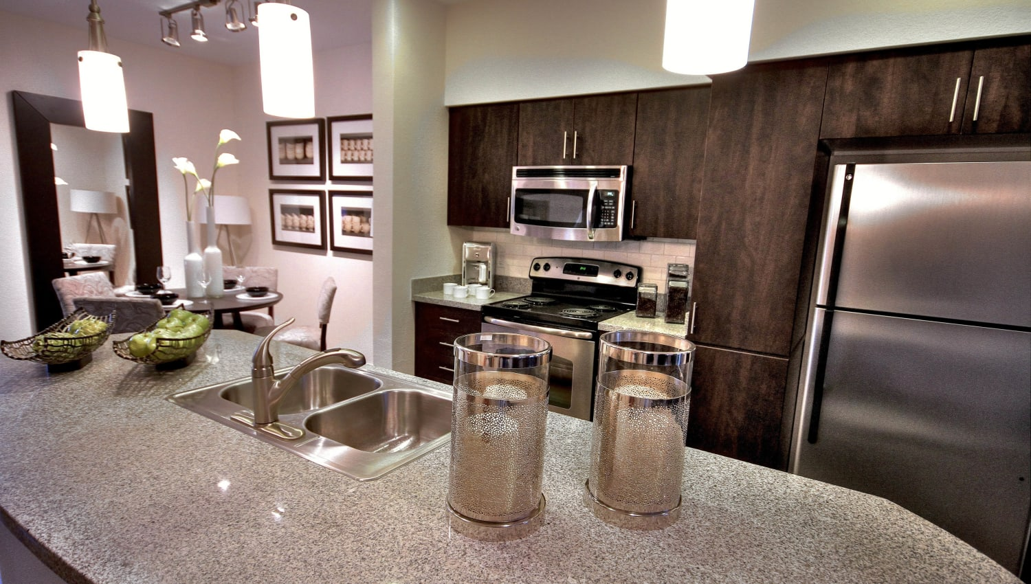 Island with a granite countertop and stainless-steel appliances in a model apartment at Redstone at SanTan Village in Gilbert, Arizona
