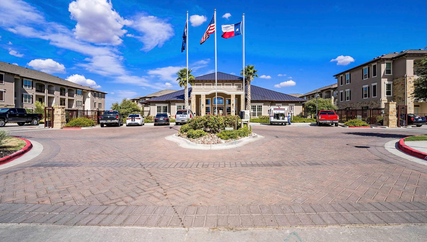 Flags and professionally maintained landscaping at the entrance to Sundance Creek in Midland, Texas