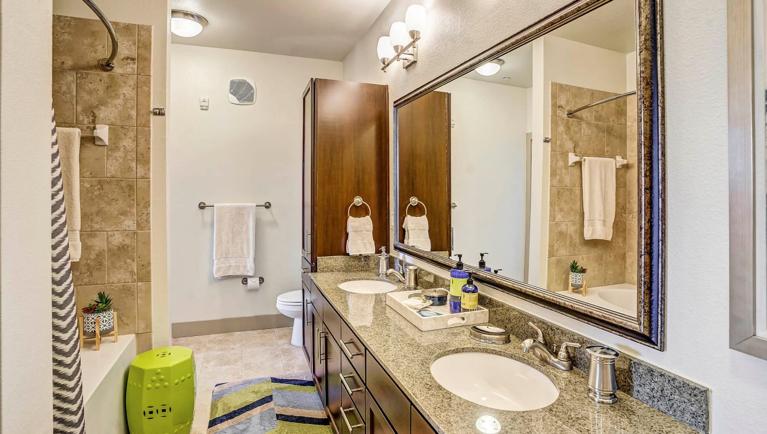 Custom tiled shower and a granite countertop in a model home's master bathroom at Sundance Creek in Midland, Texas