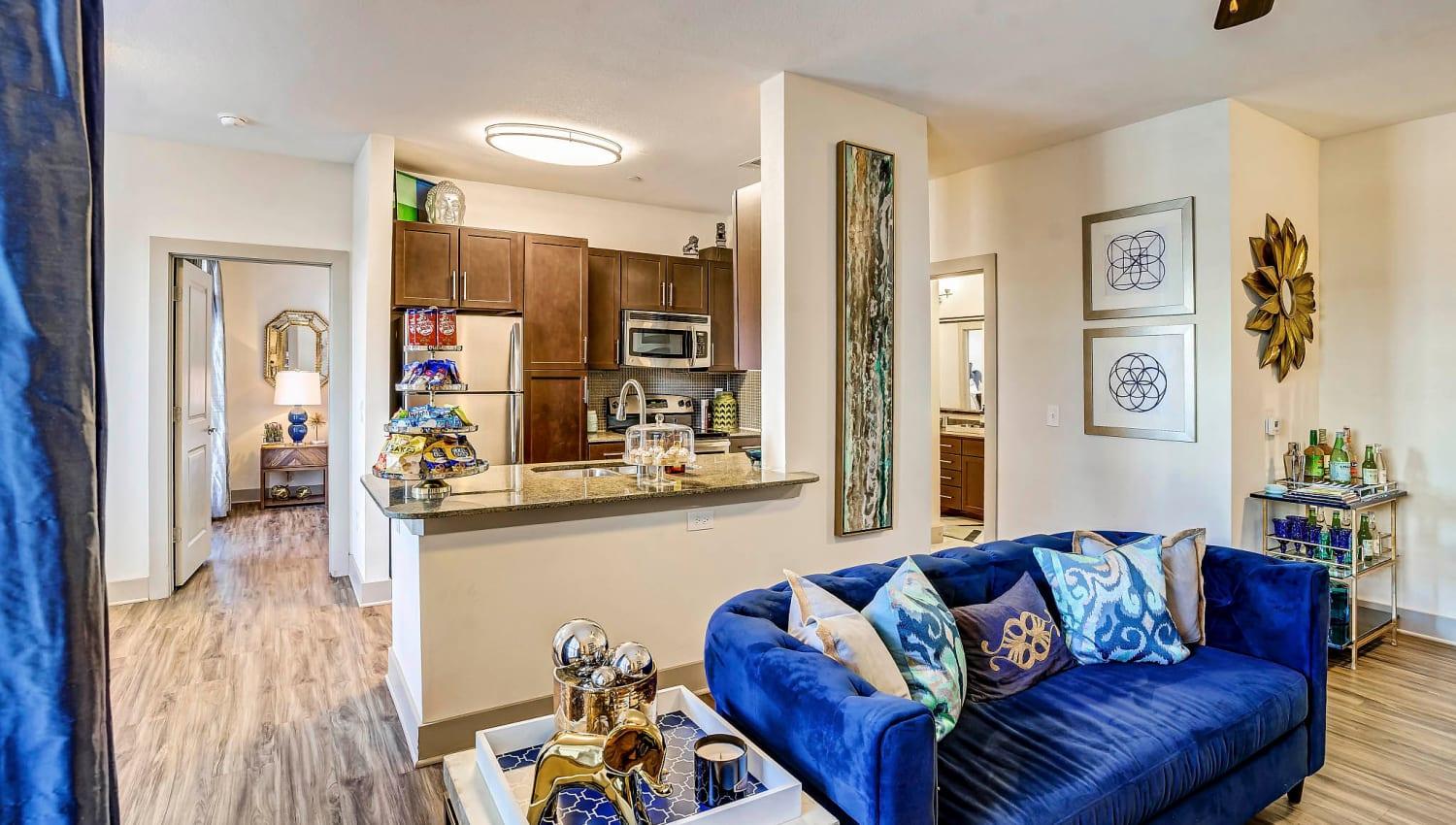 Model home with a kitchen breakfast bar near the living area at Sundance Creek in Midland, Texas