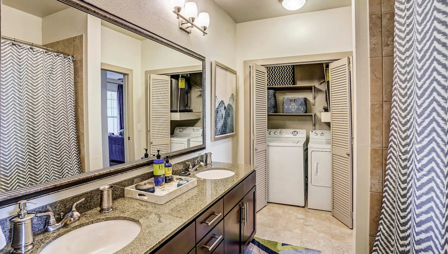 Dual sinks and adjacent laundry room in a model home's bathroom at Sundance Creek in Midland, Texas