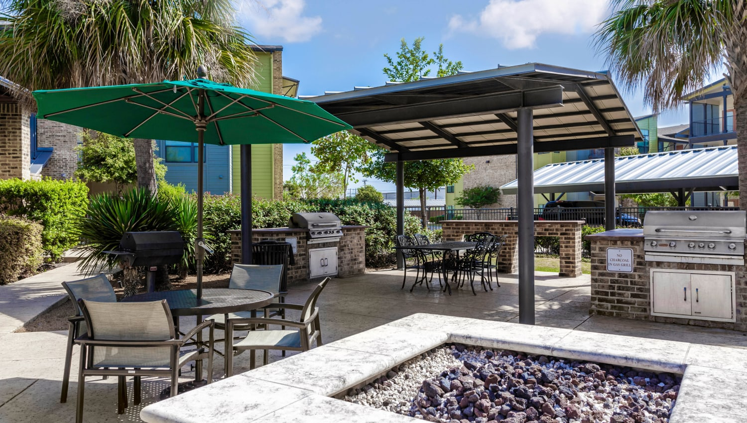 Fire pit area with shaded seating nearby at Tacara at Westover Hills in San Antonio, Texas
