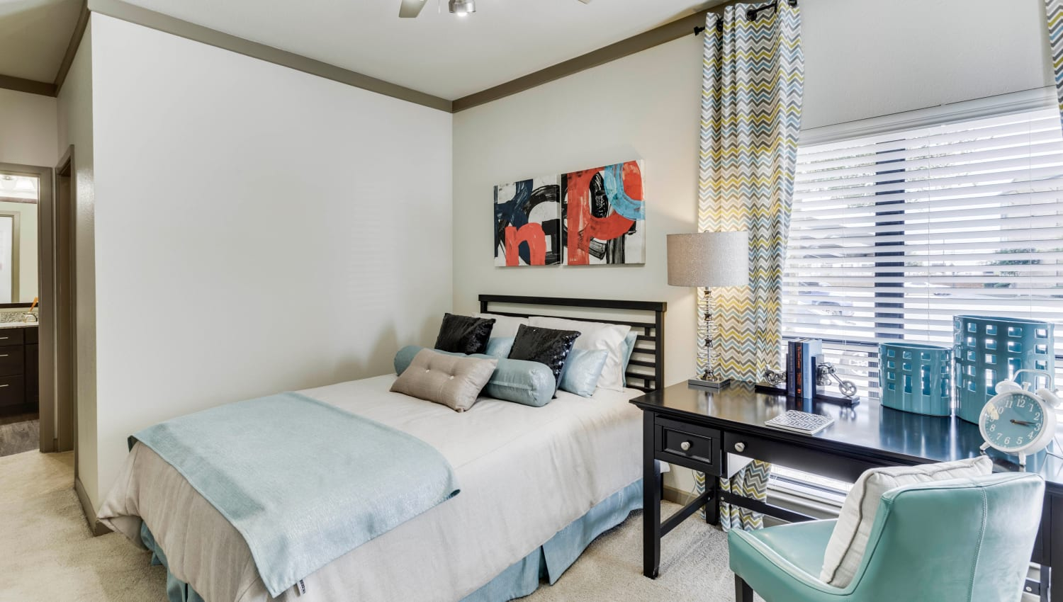 Well-furnished master bedroom with plush carpeting in a model apartment at Tacara at Westover Hills in San Antonio, Texas