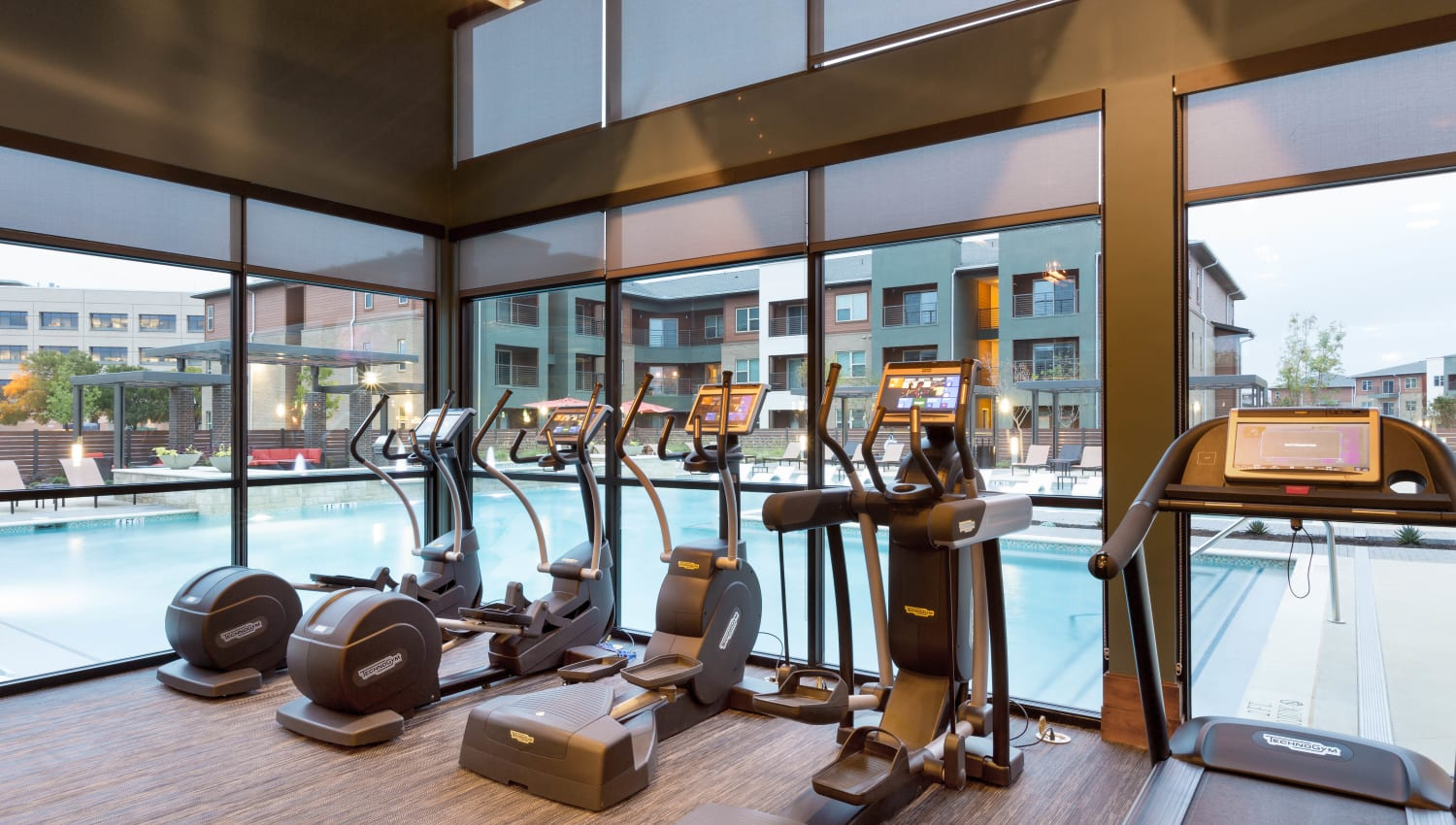 Cardio equipment with a prime view of the swimming pool at The Davis in Fort Worth, Texas