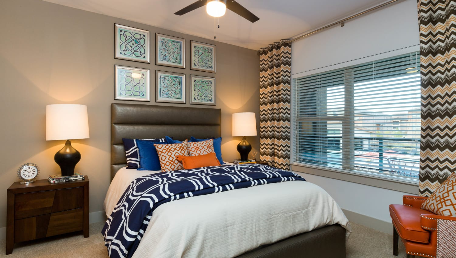 Large bay windows and colorful decor in a model home's bedroom at The Davis in Fort Worth, Texas