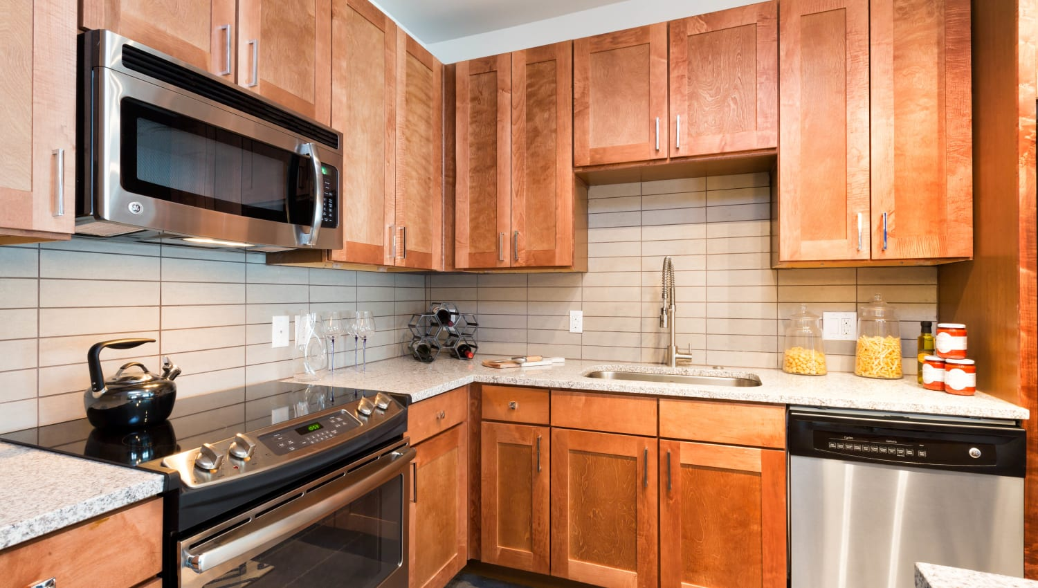 Cherry wood cabinetry in a model apartment's kitchen at The Davis in Fort Worth, Texas