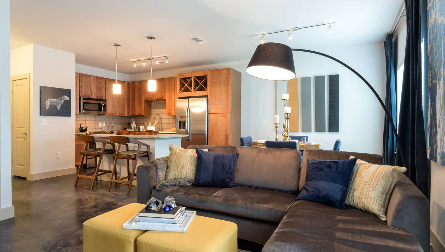Well-furnished living area with the kitchen in the background of a model apartment at The Davis in Fort Worth, Texas