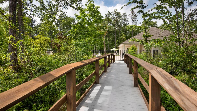 Wooden bridge through mature trees at The Enclave in Brunswick, Georgia