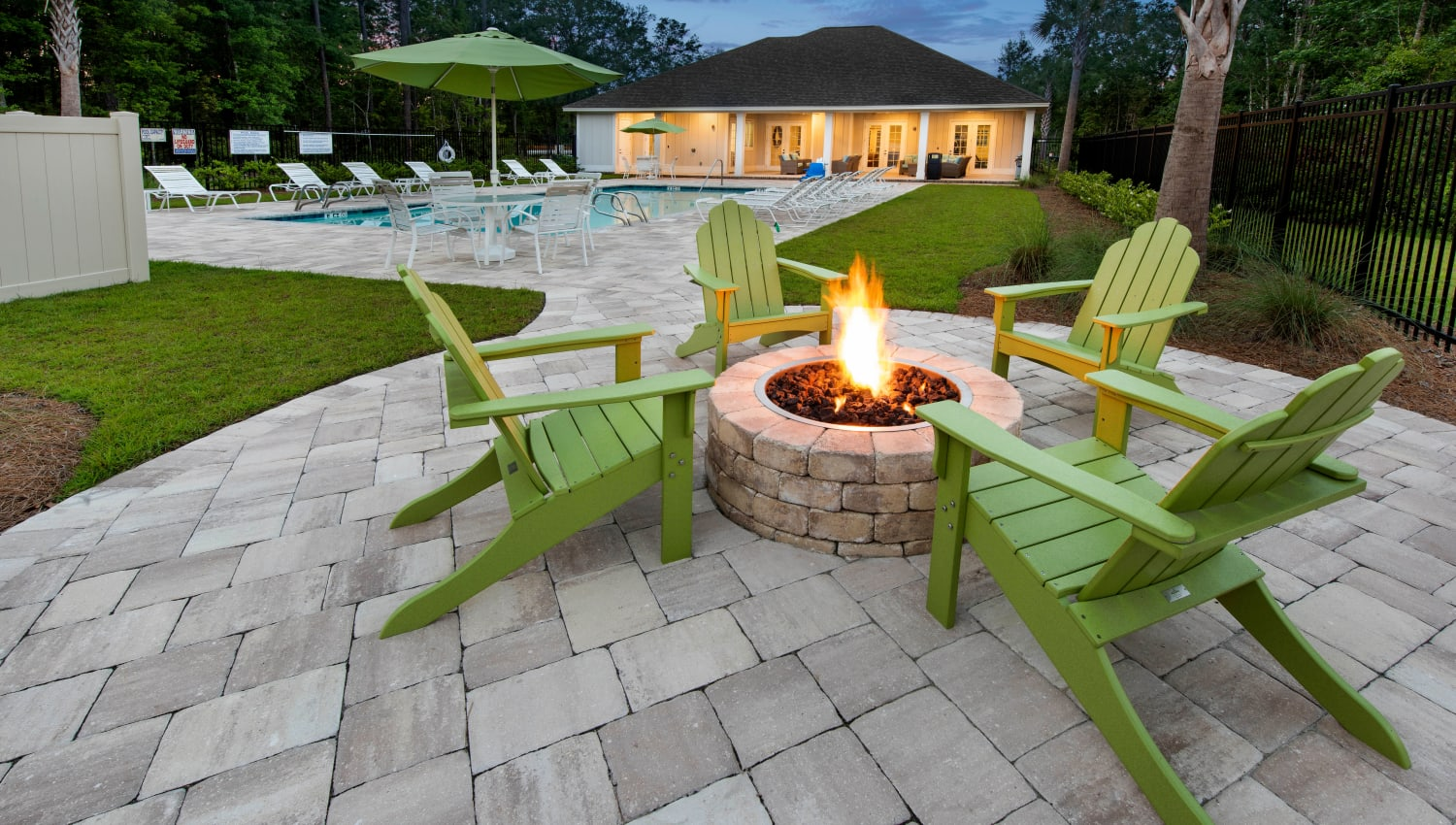 Adirondack chairs around the fire pit at dusk at The Enclave in Brunswick, Georgia