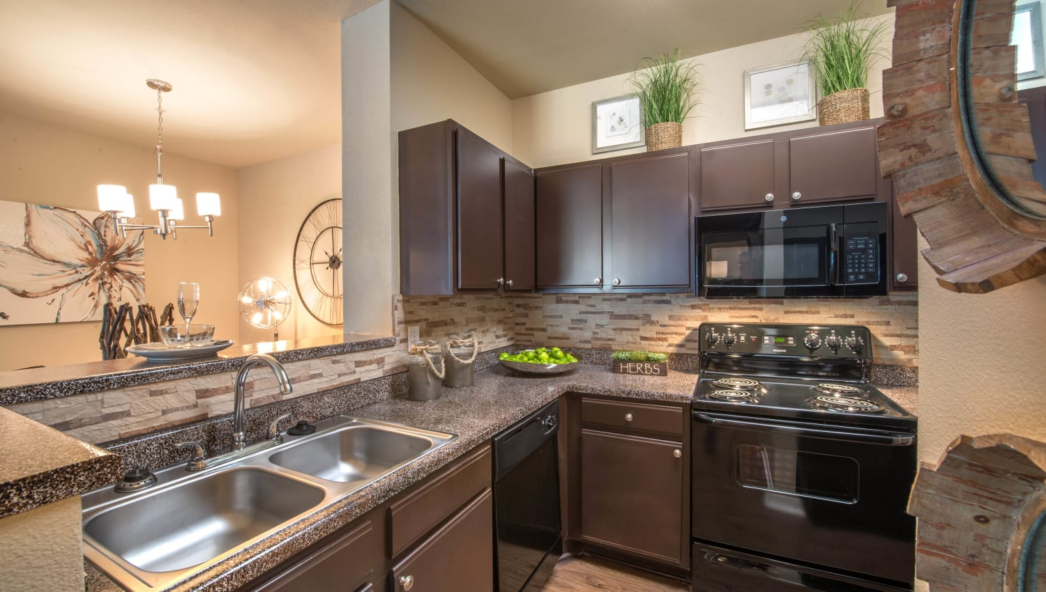 Dual-basin sink and granite countertops in a model home's kitchen at The Ranch at Shadow Lake in Houston, Texas