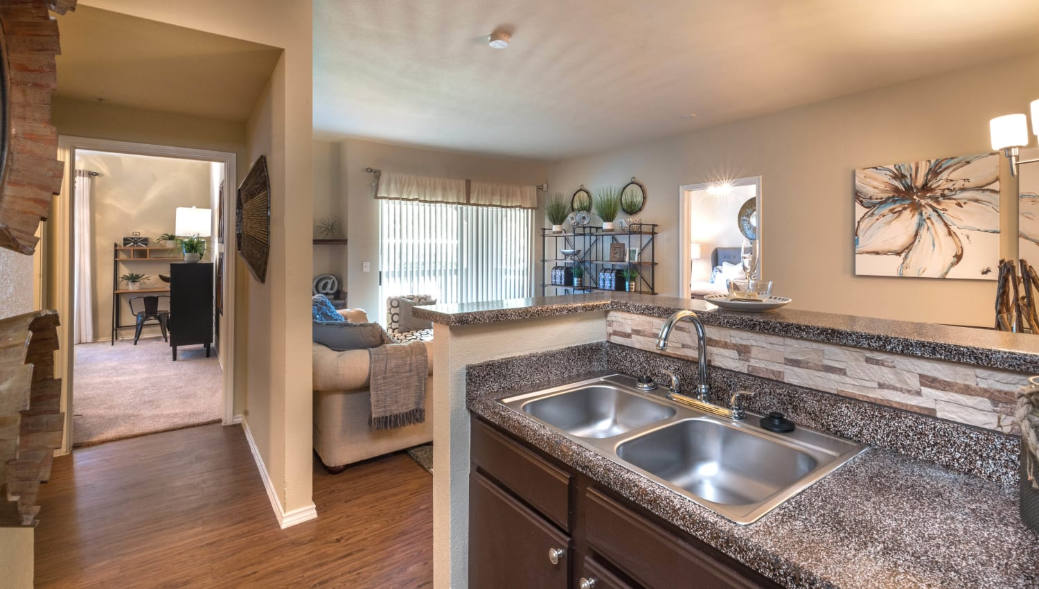 View of the living area over the kitchen's breakfast bar in a model home at The Ranch at Shadow Lake in Houston, Texas