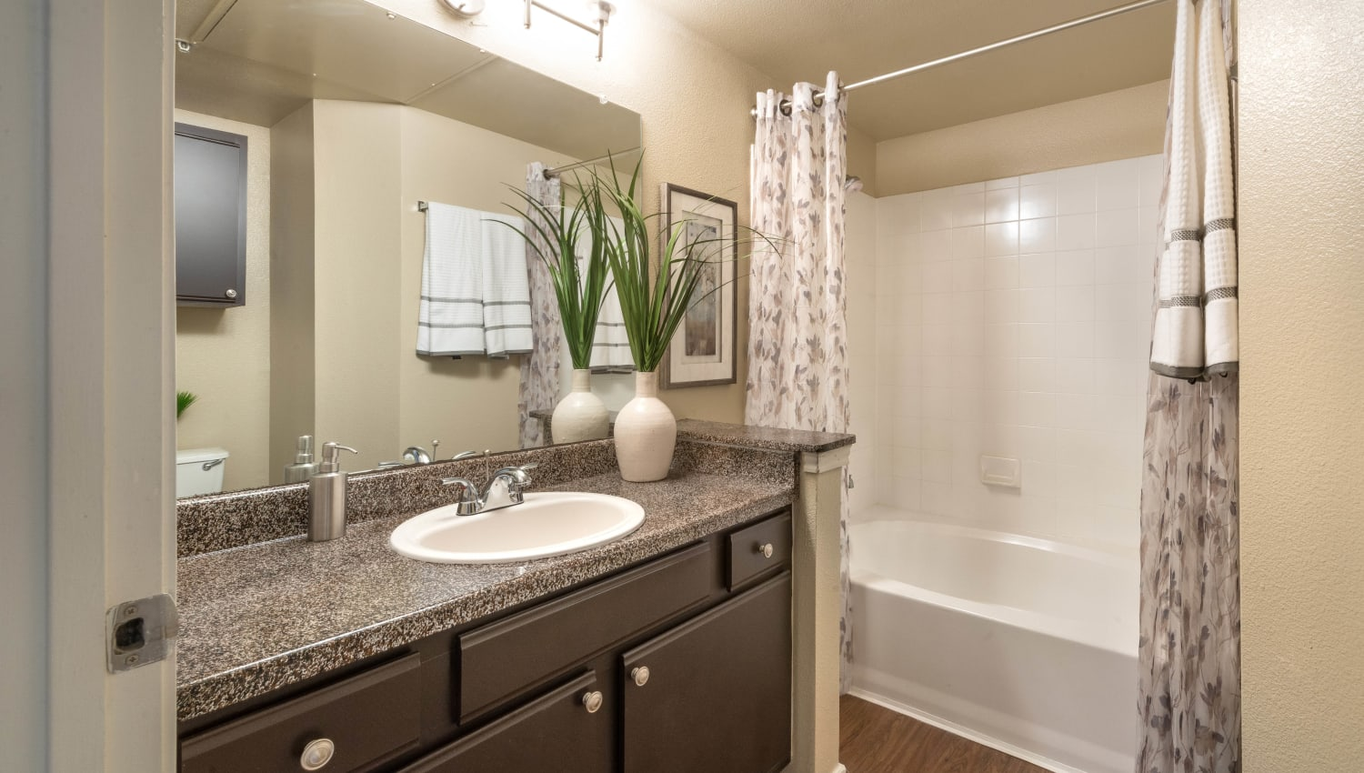 Tiled shower and a granite countertop in a model apartment's bathroom at The Ranch at Shadow Lake in Houston, Texas