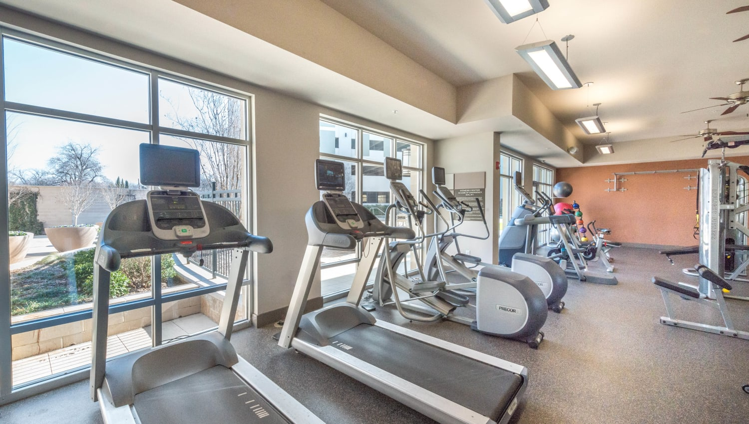 Treadmills and stair climbers in the onsite fitness center at Union At Carrollton Square in Carrollton, Texas