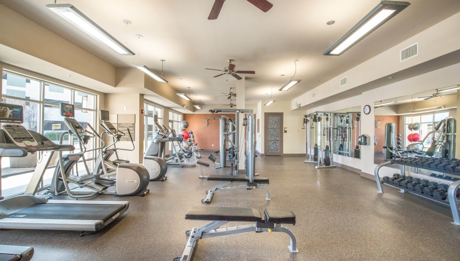 Cardio machines and free weights in the fitness center at Union At Carrollton Square in Carrollton, Texas