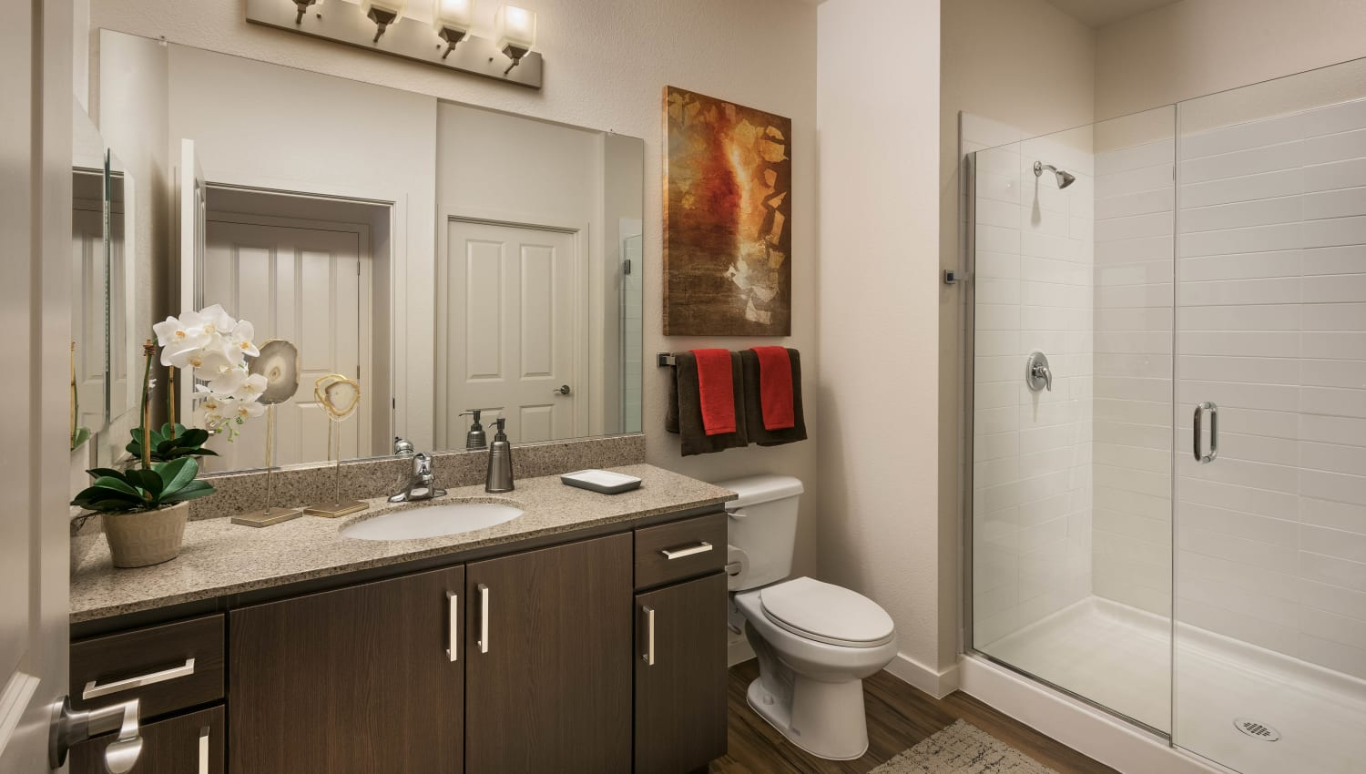 Large vanity mirror and a stand-up shower in a model apartment's bathroom at Vistara at SanTan Village in Gilbert, Arizona