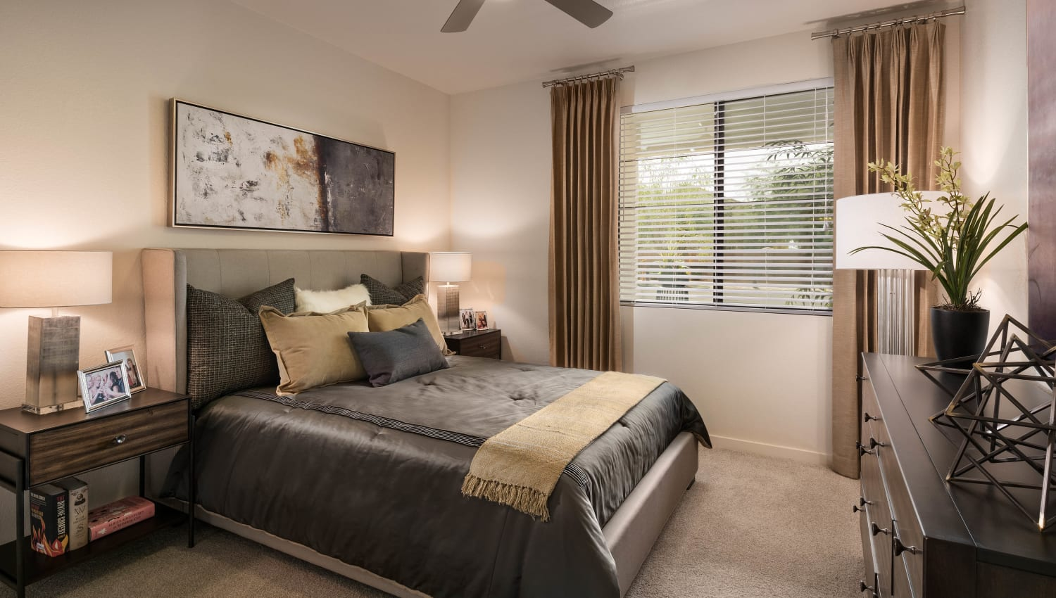 Well-furnished master bedroom with plush carpeting in a model home at Vistara at SanTan Village in Gilbert, Arizona