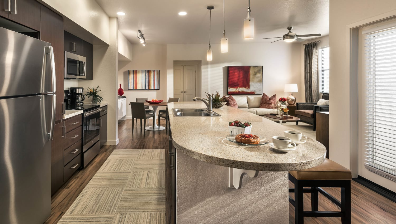Model home's gourmet kitchen with an island and custom wood cabinetry at Vistara at SanTan Village in Gilbert, Arizona