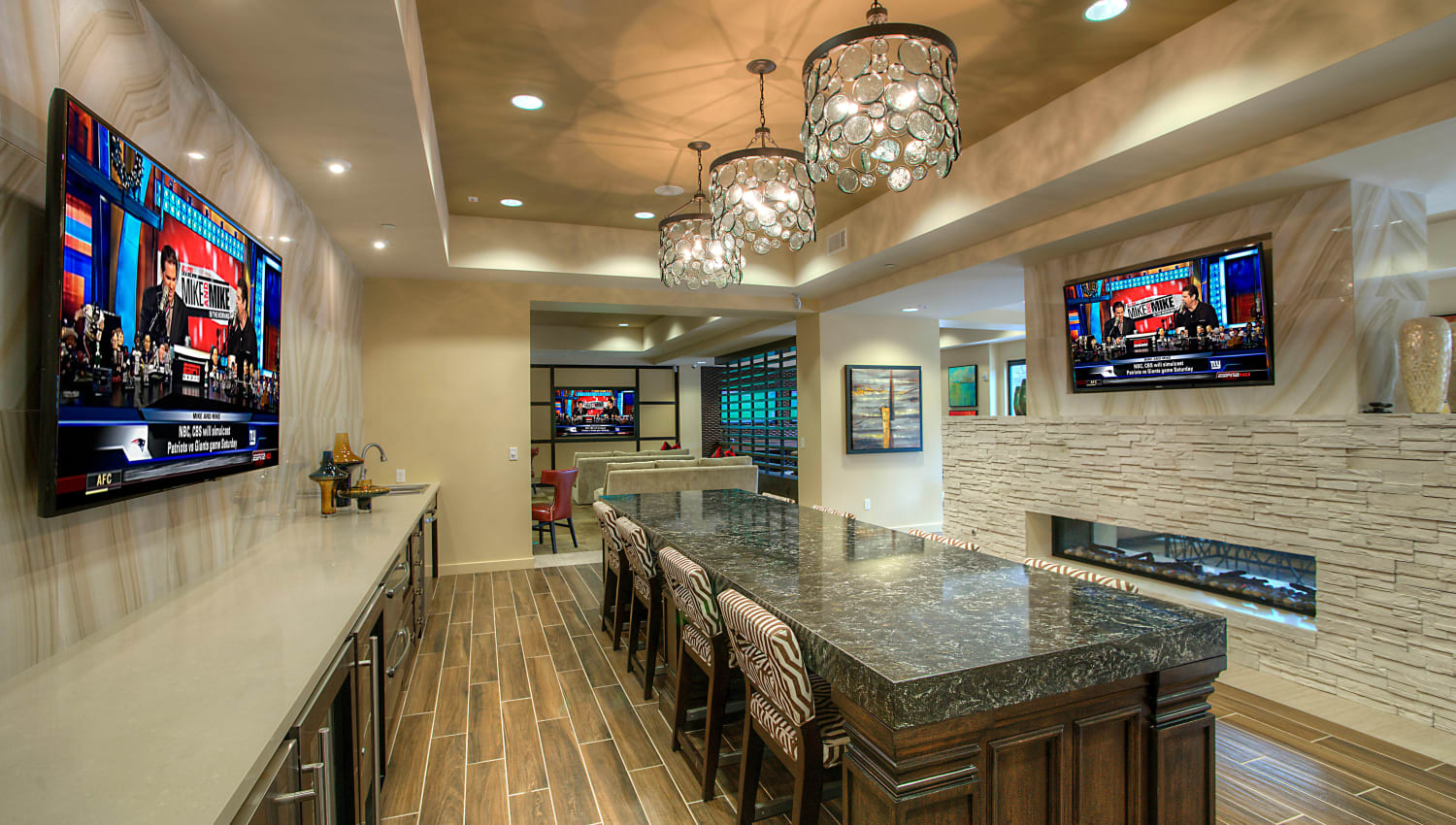 Bar seating and flatscreen TVs in the clubhouse lounge at Vistara at SanTan Village in Gilbert, Arizona