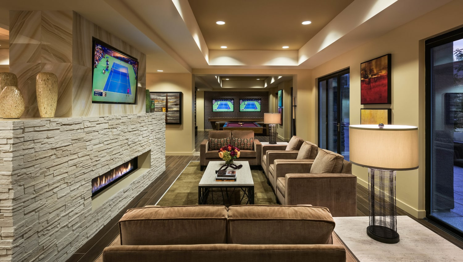 Comfortable lounge area in front of the fireplace in the clubhouse at Vistara at SanTan Village in Gilbert, Arizona